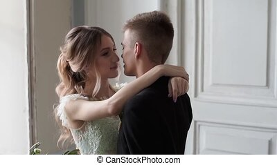 Wedding couple indoors is hugging each other