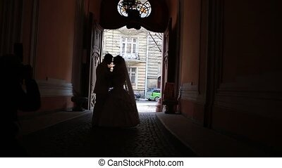 wedding couple kissing in a dark arch and poses for the...