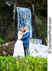 Wedding couple kissing in front of a waterfall