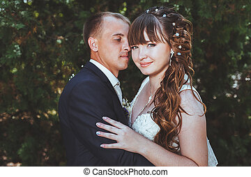 wedding couple kissing in green summer park. bride and groom kissing, standing together outdoors, hugging among green trees. Bride holding wedding bouquet of flowers