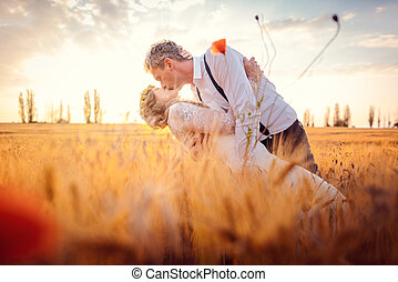 Wedding couple kissing in romantic setting on a wheat field