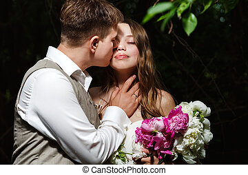 Wedding couple kissing in the park