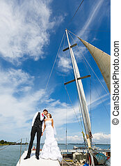Wedding couple kissing on a yacht