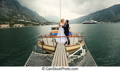 Wedding couple kissing on the stern of the ship sailing on the sea in Montenegro, Budva