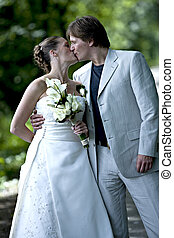 Wedding couple kissing - Wedding couple posing with a kiss