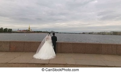 Wedding couple looking at Petr and Paul fortress Saint-Petersburg