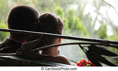 Wedding couple looking at the rain through the window, rear view