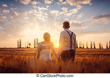 Wedding couple looking into a beautiful sunset