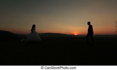Wedding couple meets on the top of the hill in the mountains on sunset