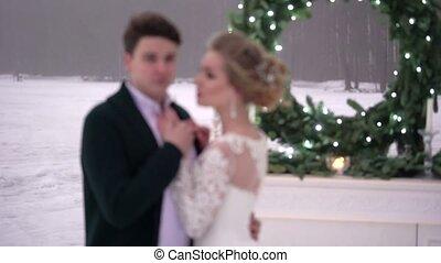 Wedding couple near fireplace decoration on frozen lake