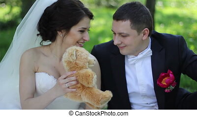 wedding couple on picnic in park with teddy bear