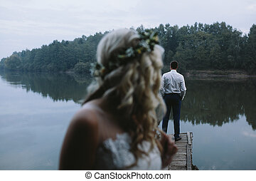 Wedding couple on the old wooden pier posing for the camera