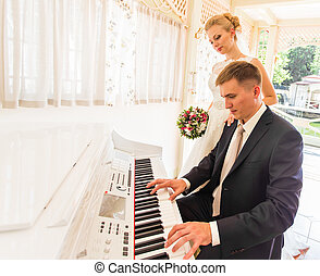 wedding couple playing on a piano in the room