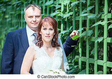Wedding couple portrait with green fence, copyspace