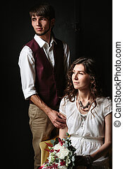 Wedding couple posing in the dark interior