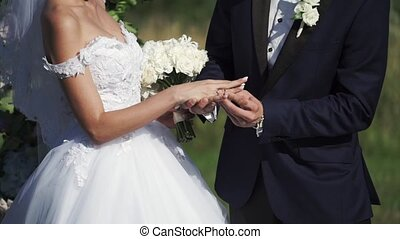 Wedding couple put on wedding rings at ceremony outdoors at...