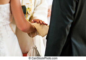 Wedding couple receiving blessing from priest