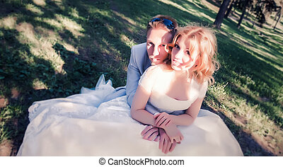 Wedding couple sit on the grass in the forest