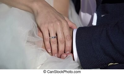 Wedding couple sitting and holding hands outdoors