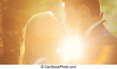 Wedding couple softly kissing on sunset close up