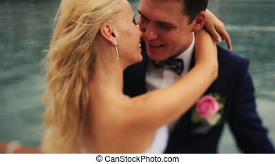 Wedding couple softly kissing on the yacht close up