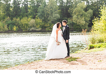 Wedding couple standing and hugging near lake.