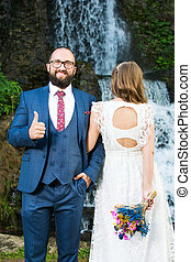 Wedding couple standing in front of a waterfall