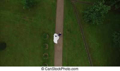 Wedding couple walking in park in the rain.