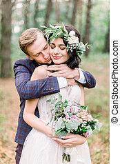 Wedding couple walking in the forest, handsome man ebracing pretty woman. Rustic wedding walk outdoors