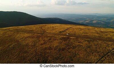 Wedding walk. The groom follows his wife on the mountain top of Mount Gemba. Ukrainian Carpathian Mountains. Aerial view.