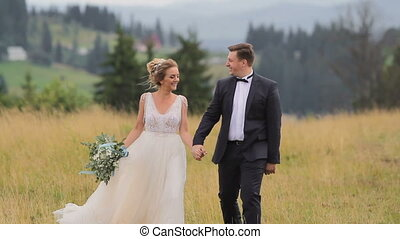 Beautiful young wedding couple walking before mountains landscape