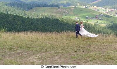 Wedding Couple Walks near Mountain Canyon