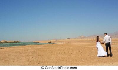 Wedding couple walks on the beach in Egypt. Exotic honeymoon