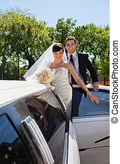 Wedding Couple with Limousine - Cheerful newly wed couple...
