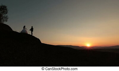 Wedding cuople kissing on the sunset in the mountains