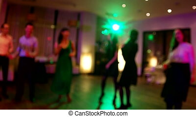 Wedding. Dancing bride and groom, couples and guests. Blurred background. Slow motion clip.