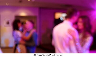 Wedding. Dancing bride and groom, couples and guests. Blurred background.