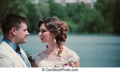 Wedding day. Beautiful couple enjoy their happiness standing on a quay, kissing. Wedding outfit, bouquet