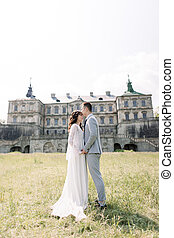 wedding day. Bride and groom, Chinese couple, walking near an old castle, holding hands and hugging