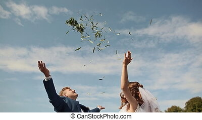 Wedding day. Fireworks from tree leaves. The groom lifts the bride happy and circling a happy wife.