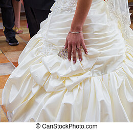 Wedding day. Hand of bride with a wedding ring on her dress