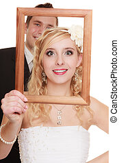 Wedding day. Happy couple in wooden frame isolated