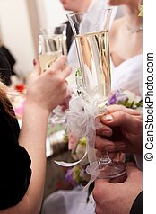 wedding decorated glasses in hands of groom and bride
