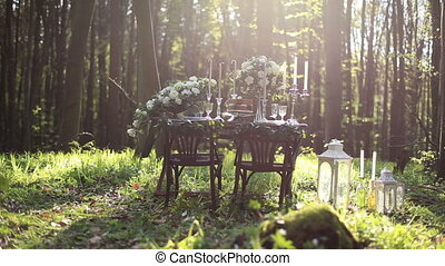 Wedding decorated table setted for two on nature in the forest. Wedding decoration of white roses bouquets and vintage candles with lanterns.