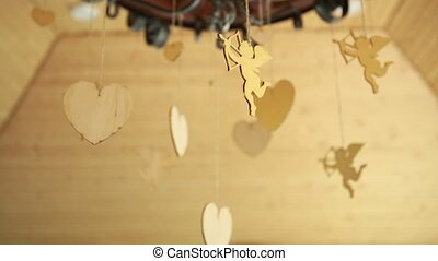 wedding decoration in the form of wooden hearts and Cupid