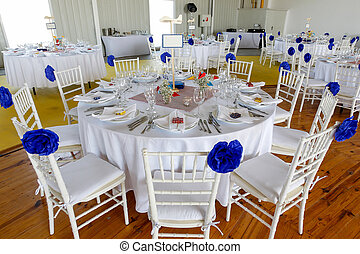 Circle dinner table served with white crockery and decorated with colorful objects.
