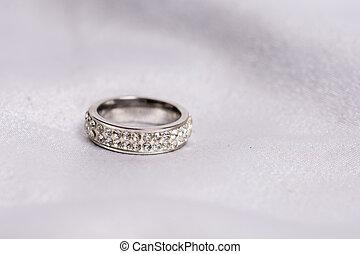 Wedding diamond ring on white satin background