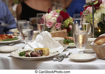 wedding food on a table with a bouquet of flowers in the background. Shallow depth of field with the focus on the food