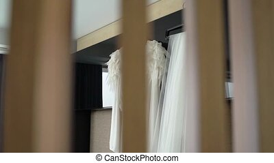 Wedding dress and bridal veil in bedroom at the morning