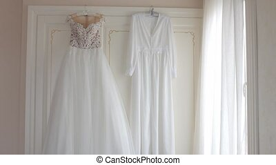 Wedding dress and cape hanging on hangers in the apartment -...